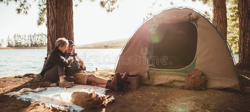 享用一杯酒的成熟夫妇在他们的露营地 免版税库存图片