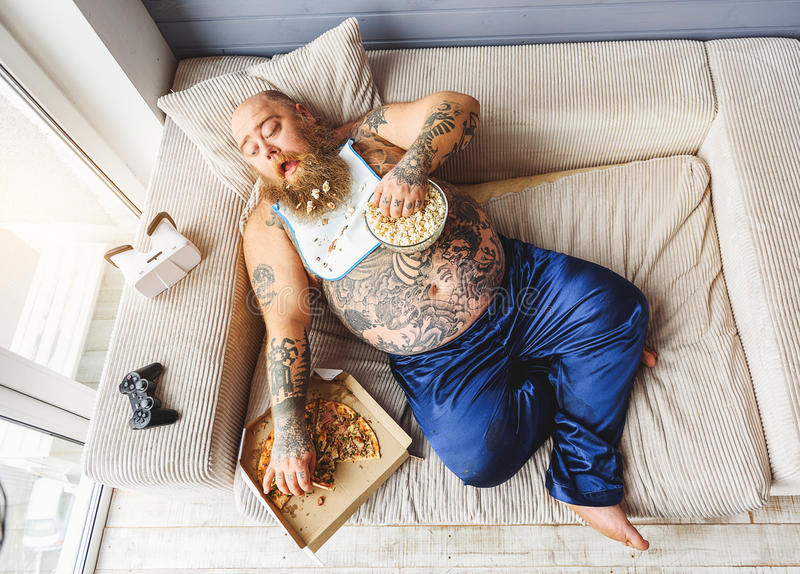 享用不健康的食物的男性暴食者 免版税库存照片