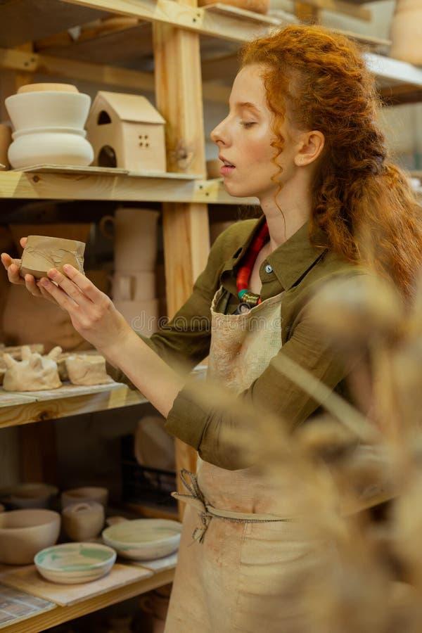 享用不同的黏土形象和罐的殷勤姜女孩 免版税图库摄影