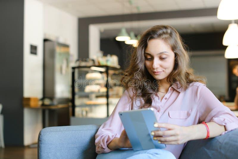 享用与快速的互联网由片剂和坐在咖啡馆的年轻白种人女孩 免版税库存图片