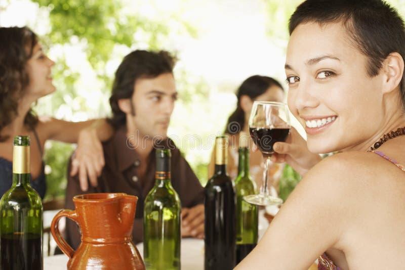 享用与朋友的妇女红葡萄酒在背景中 免版税库存照片