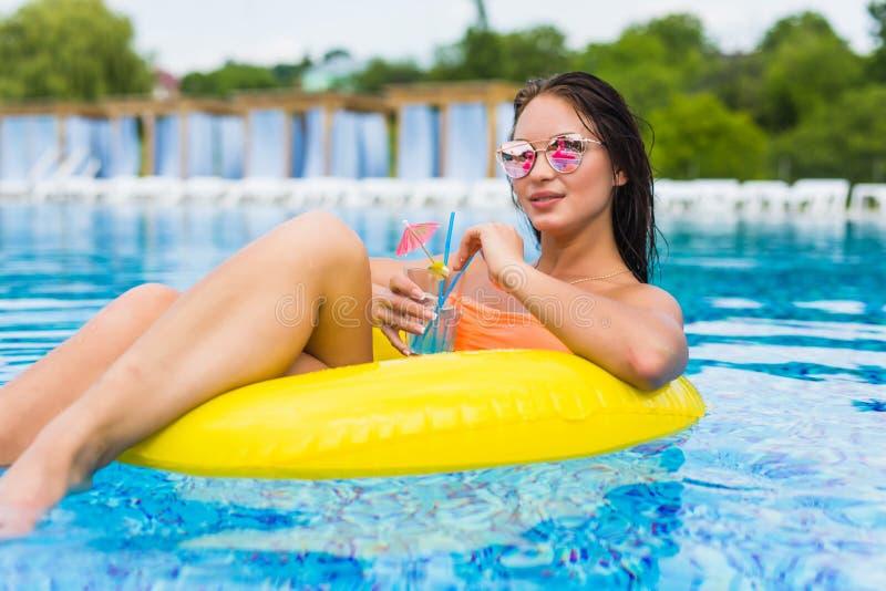 享用与橡胶环和鸡尾酒的少妇在游泳池 库存图片