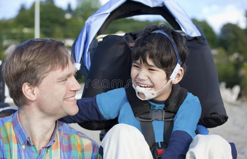 享用与残疾儿子的父亲海滩 免版税库存照片