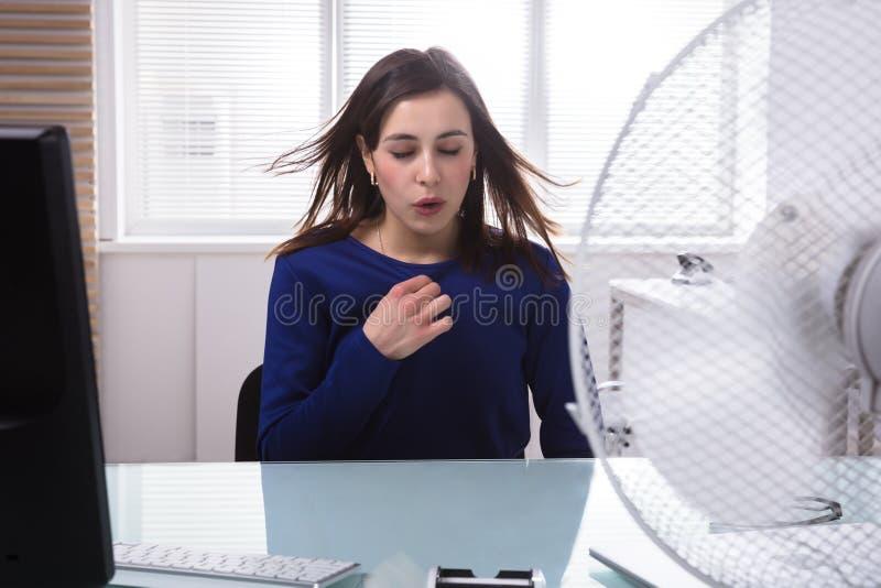 享用与电扇的女实业家微风 库存照片