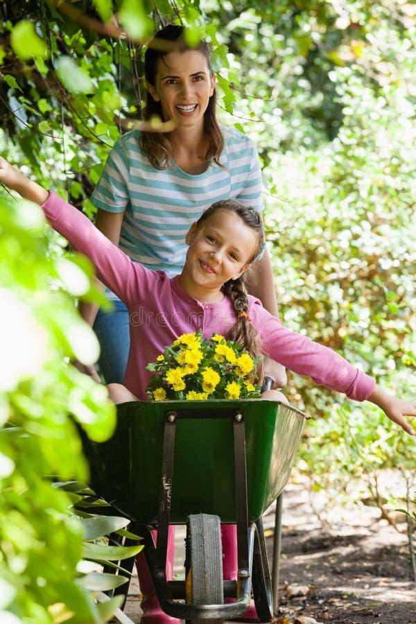 享用与胳膊的女孩被伸出,当推挤独轮车时的微笑的母亲 库存照片