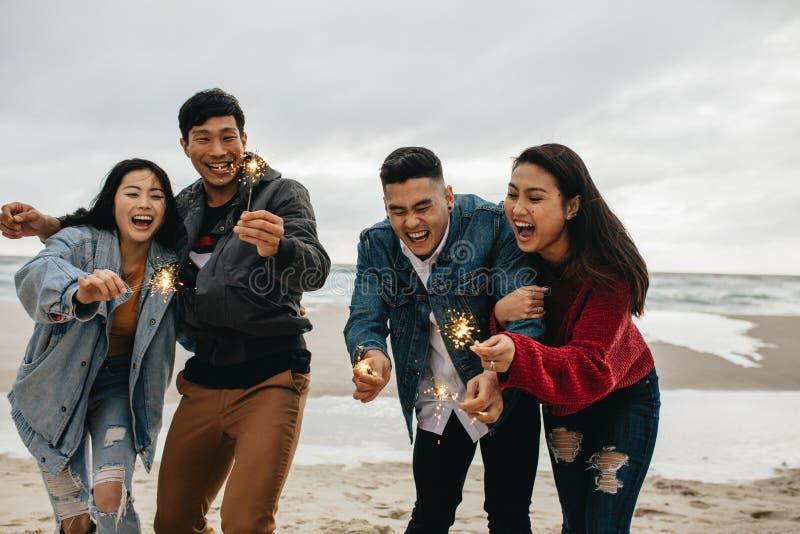 享用与闪烁发光物的亚裔朋友在海滩 免版税库存照片