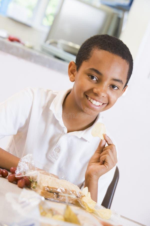 享用他的午餐学校男小学生的自助餐厅 免版税图库摄影