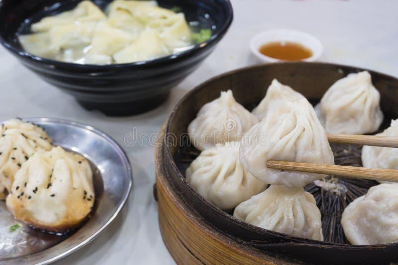 享用传统上海食物包括饺子、馄饨和xiaolongbao 免版税库存照片