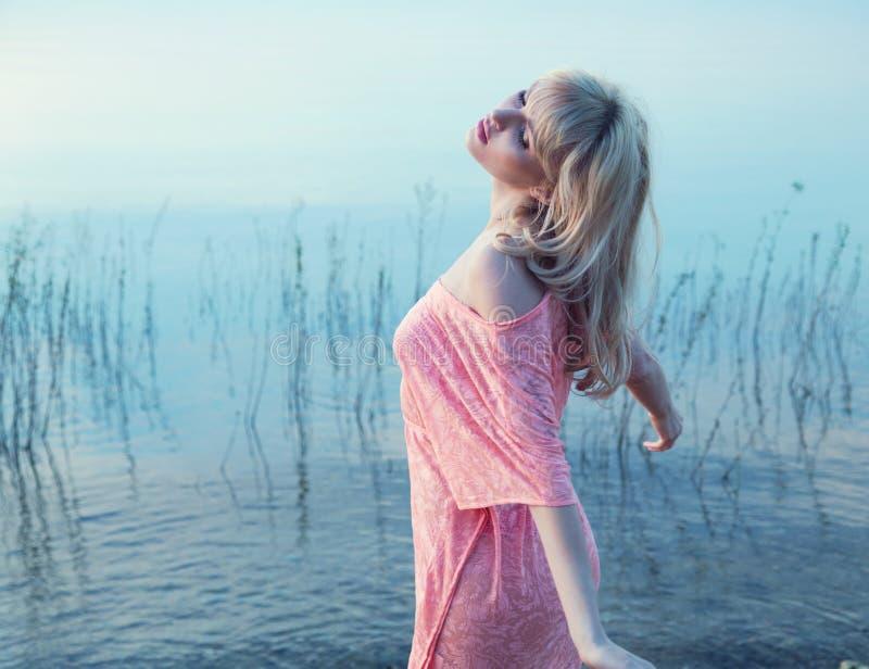 享用冷的湖水的肉欲的白肤金发的女孩 免版税库存照片