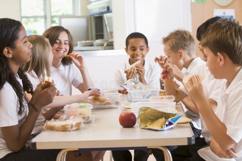 享用午餐他们学校的学童 免版税库存照片