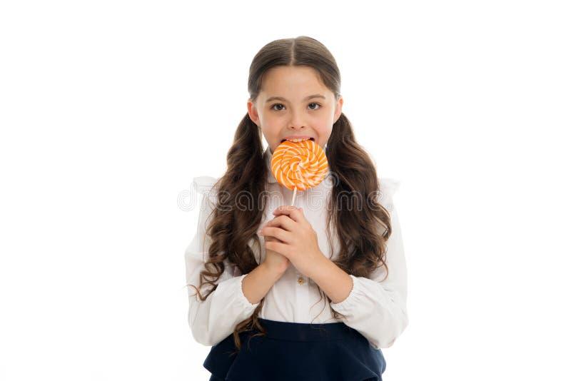 享用可口糖果 女孩逗人喜爱的孩子马尾辫发型吃甜棒棒糖 在好适当的部分的甜点 女孩 免版税库存图片