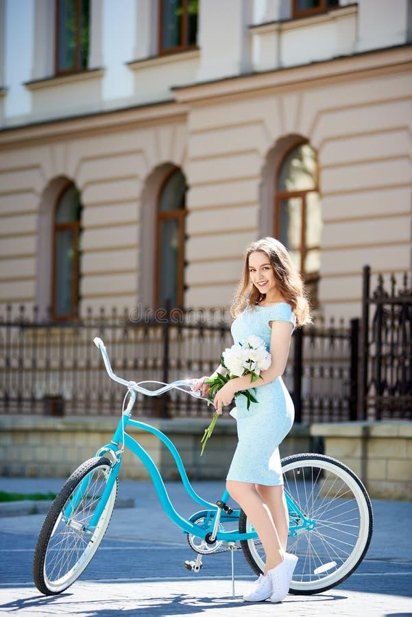 享用可爱的少妇骑她的自行车 图库摄影