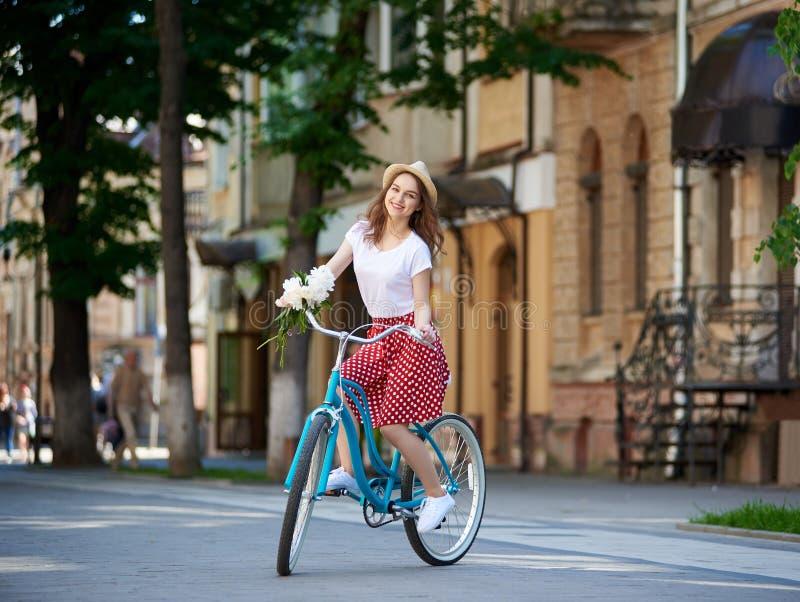享用可爱的少妇骑她的自行车 免版税库存照片
