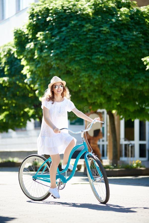 享用可爱的少妇骑她的自行车 免版税库存图片