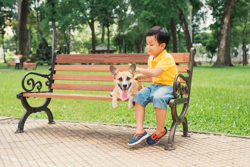 享用和使用与他的狗的亚裔小男孩在公园 免版税库存图片
