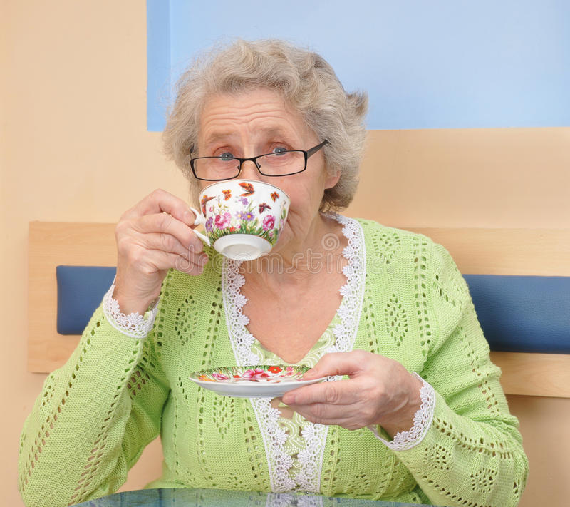享用咖啡或茶杯的老妇人 图库摄影