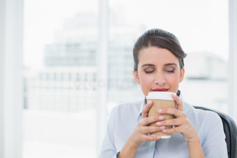 享用咖啡气味的平安的优等的棕色毛发的女实业家 免版税库存照片