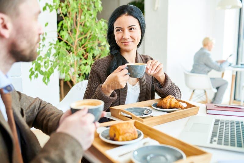 享用咖啡的俏丽的女实业家在会议上 图库摄影