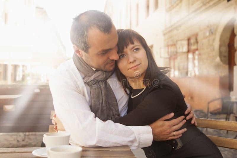 享用咖啡的年轻夫妇侧视图在室外餐馆 免版税库存照片