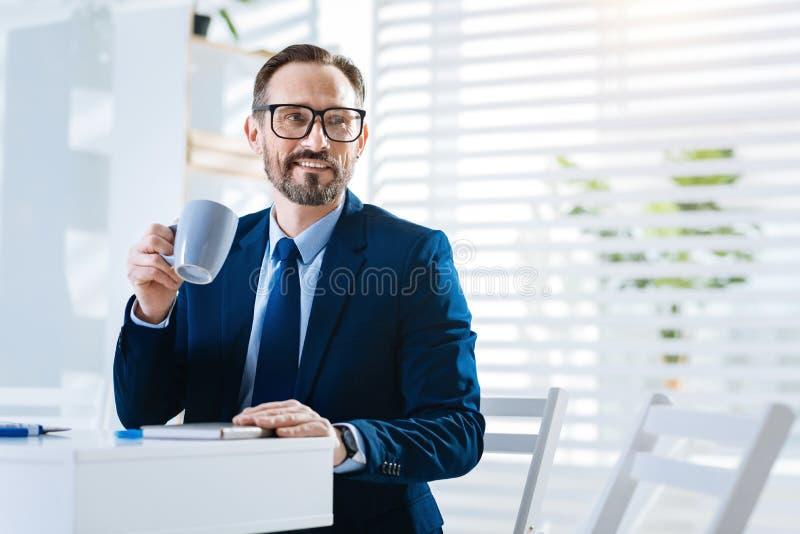 享用咖啡的快乐的乐观人 免版税库存图片