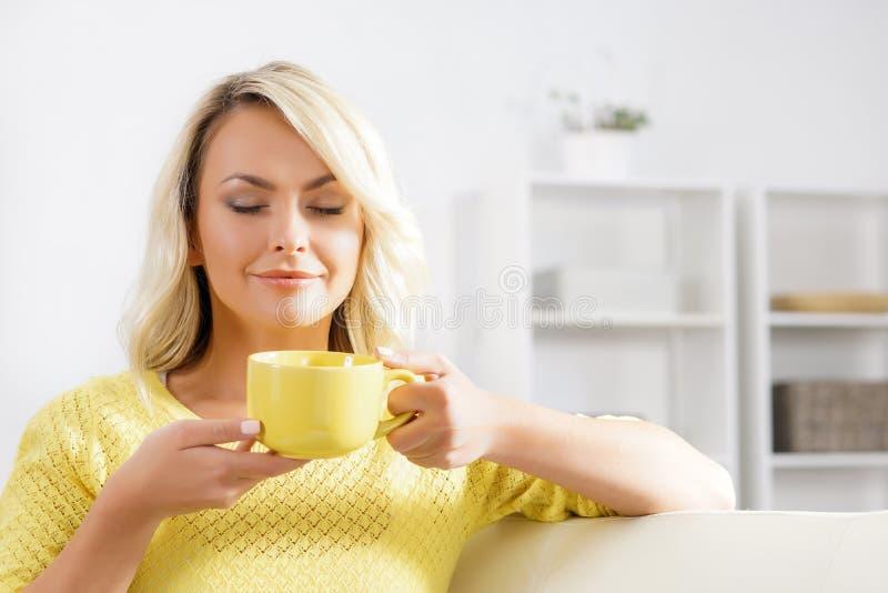 享用咖啡的气味美丽的妇女 免版税图库摄影