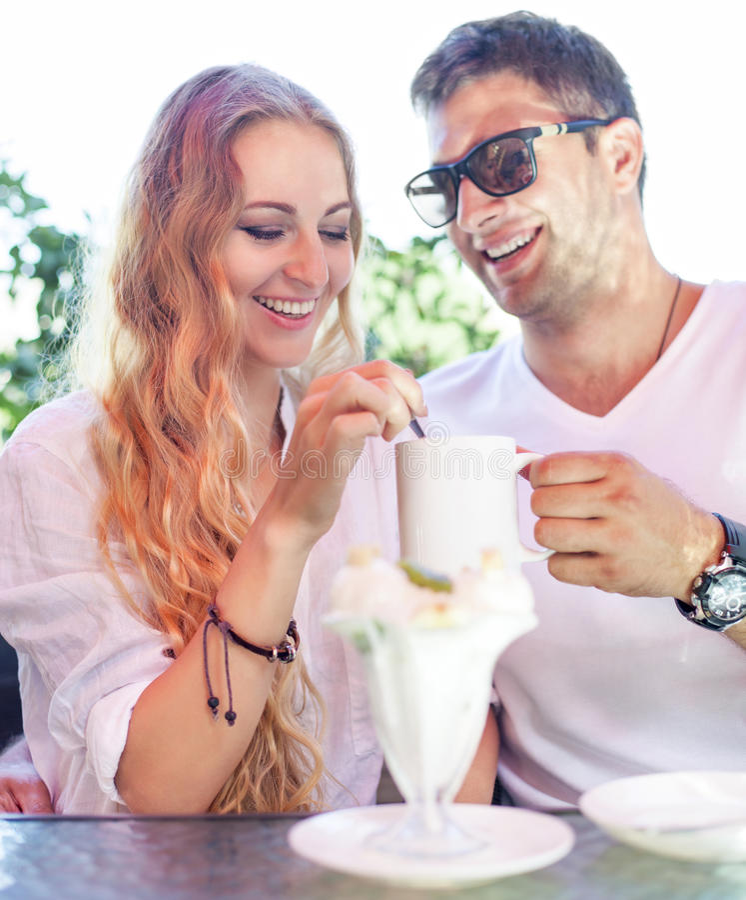 享用咖啡的年轻夫妇在街道咖啡馆 免版税库存图片