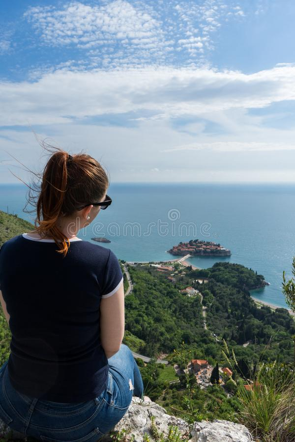 享用圣斯特凡岛海岛的红色顶头女孩小山在布德瓦,黑山 看对亚得里亚海和绿色峭壁的年轻女人 免版税库存照片