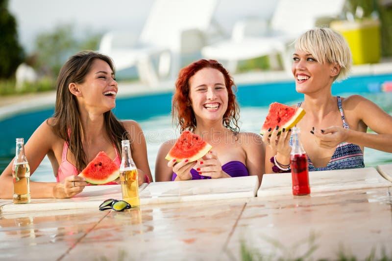 享用在与切片的水池的三个女孩西瓜和饮料 免版税库存照片