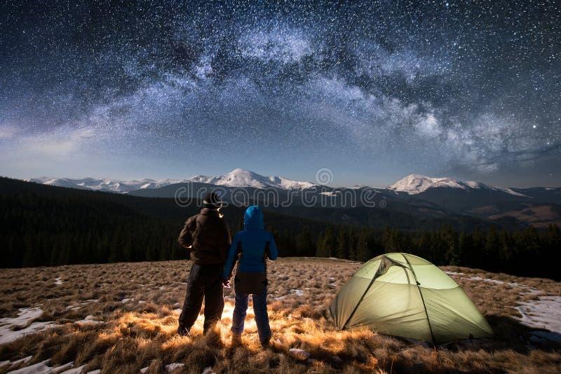 享用在充分野营的浪漫夫妇游人在晚上在美丽的夜空下星和银河 免版税库存图片