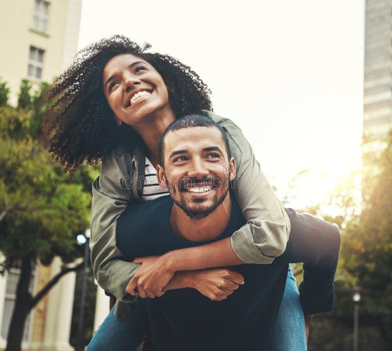 享用在城市的一对年轻夫妇的画象 免版税图库摄影