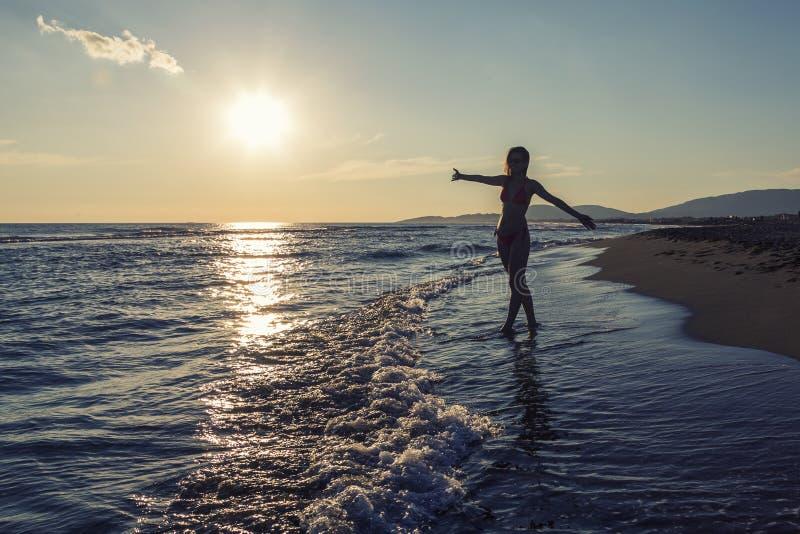 享用在夏天的女孩的剪影 免版税图库摄影