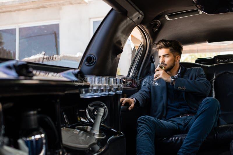 享用在大型高级轿车的年轻商人香槟 图库摄影