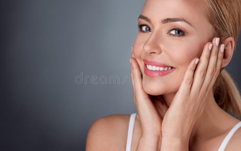 享用在她的健康皮肤的微笑的妇女 免版税库存照片