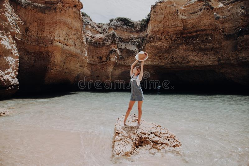 享用在岩石海滩的愉快的妇女 暑假概念 免版税库存照片