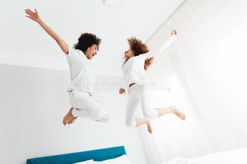 享用在床上的母亲和女儿,愉快,微笑 免版税库存图片