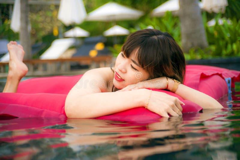 享用在度假胜地游泳池的年轻愉快和可爱的亚裔中国妇女获得乐趣在airbed微笑快乐  免版税库存图片