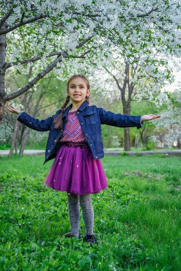 享用在春天庭院中的女孩落的瓣 免版税库存照片