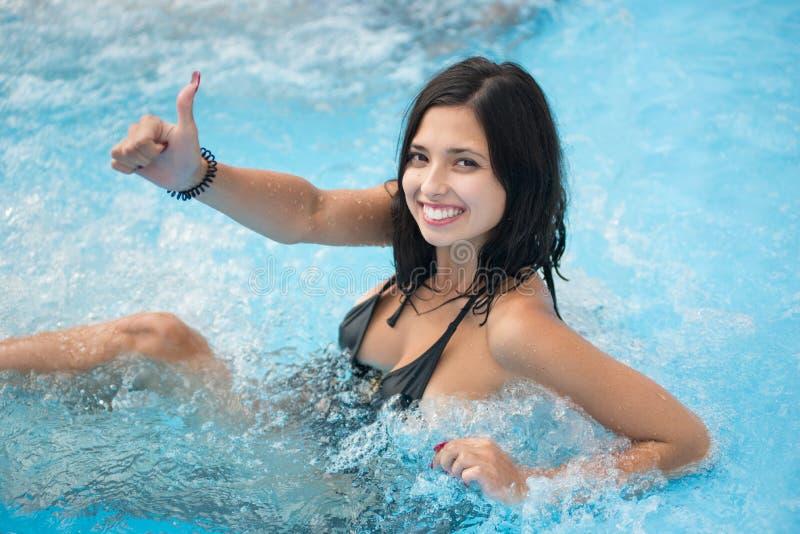 享用在极可意浴缸和显示好类的赞许姿态微笑的女孩画象在水池在手段 图库摄影