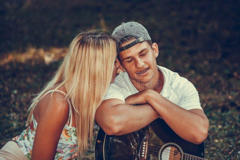 享用在浪漫野餐期间的愉快的年轻夫妇在公园 免版税库存照片