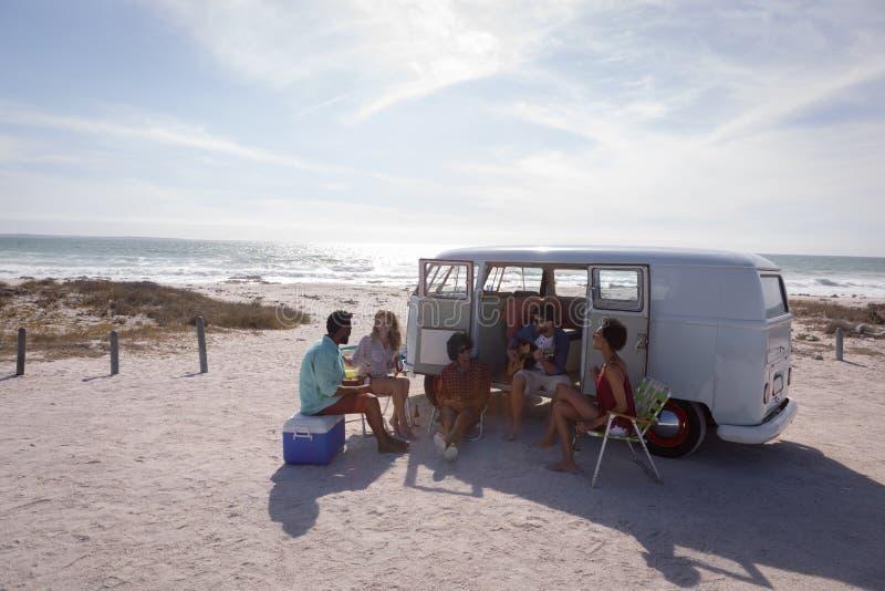 享用在海滩的小组朋友靠近他们的露营者货车 免版税库存图片