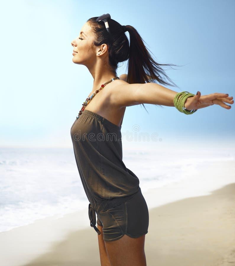 享用在海滩的俏丽的女孩夏天太阳 图库摄影