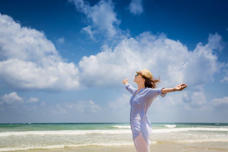 享用在海滩的愉快的妇女 免版税库存图片