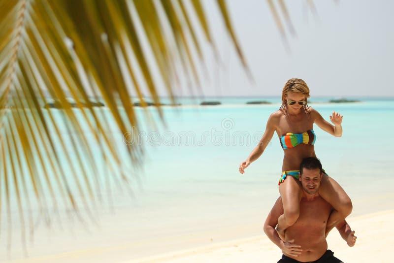 享用在海滩的愉快的美好的夫妇在马尔代夫晴天h 库存图片