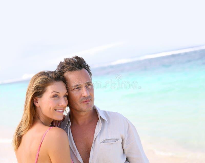 享用在海滩的爱恋的中年夫妇画象  免版税库存照片