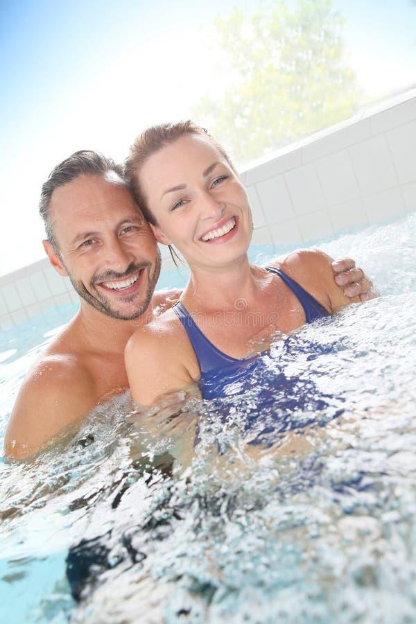 享用在温泉中心的愉快的夫妇 免版税库存图片