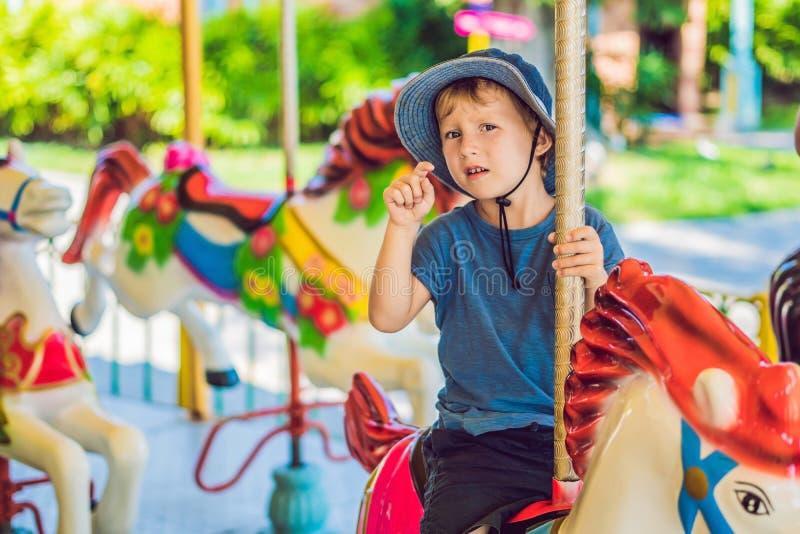 享用在游艺集市和乘坐在五颜六色的转盘房子的逗人喜爱的小男孩 库存图片