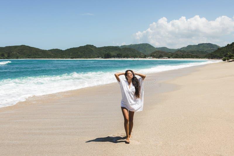 享用在白色沙滩的年轻愉快的妇女 免版税库存图片