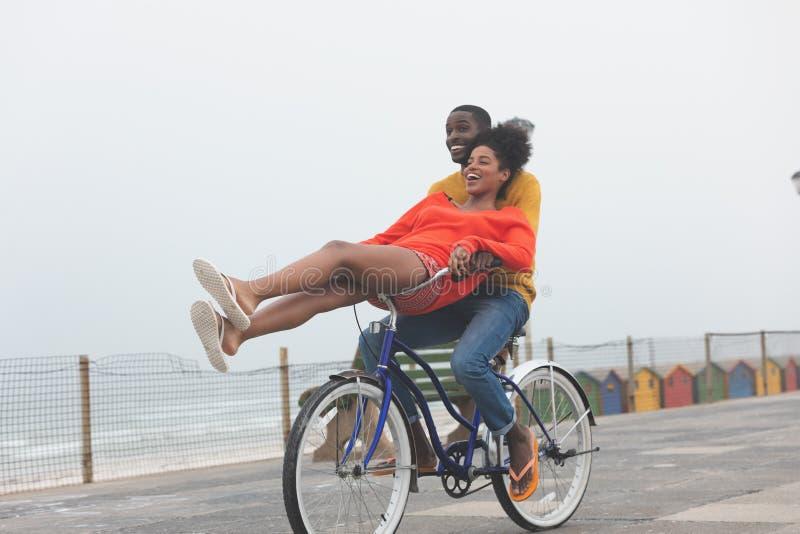 享用在自行车的夫妇,当乘坐在路面时 库存图片