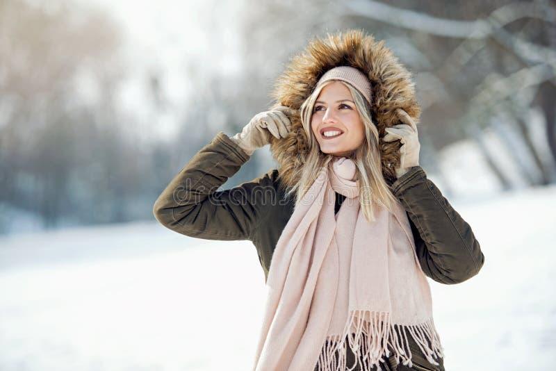 享用在雪的美丽的年轻女人 免版税图库摄影