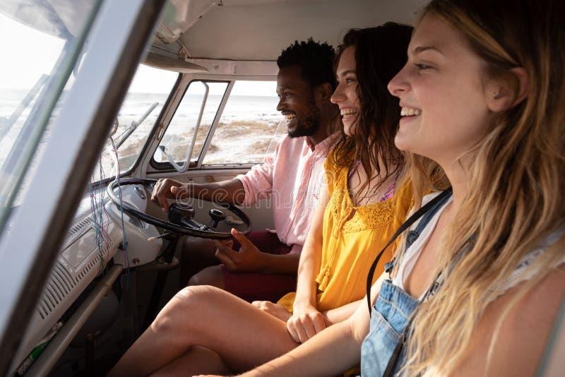 享用在露营者货车的小组朋友在海滩 免版税库存照片